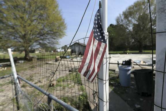 A small flag is propped on a temporary gate on Diane and Nolan Glover's property on Sunday, March 18, 2018, in Crosby, Texas. The couple, whose home is close to the Arkema plant, was destroyed by Hurricane Harvey.