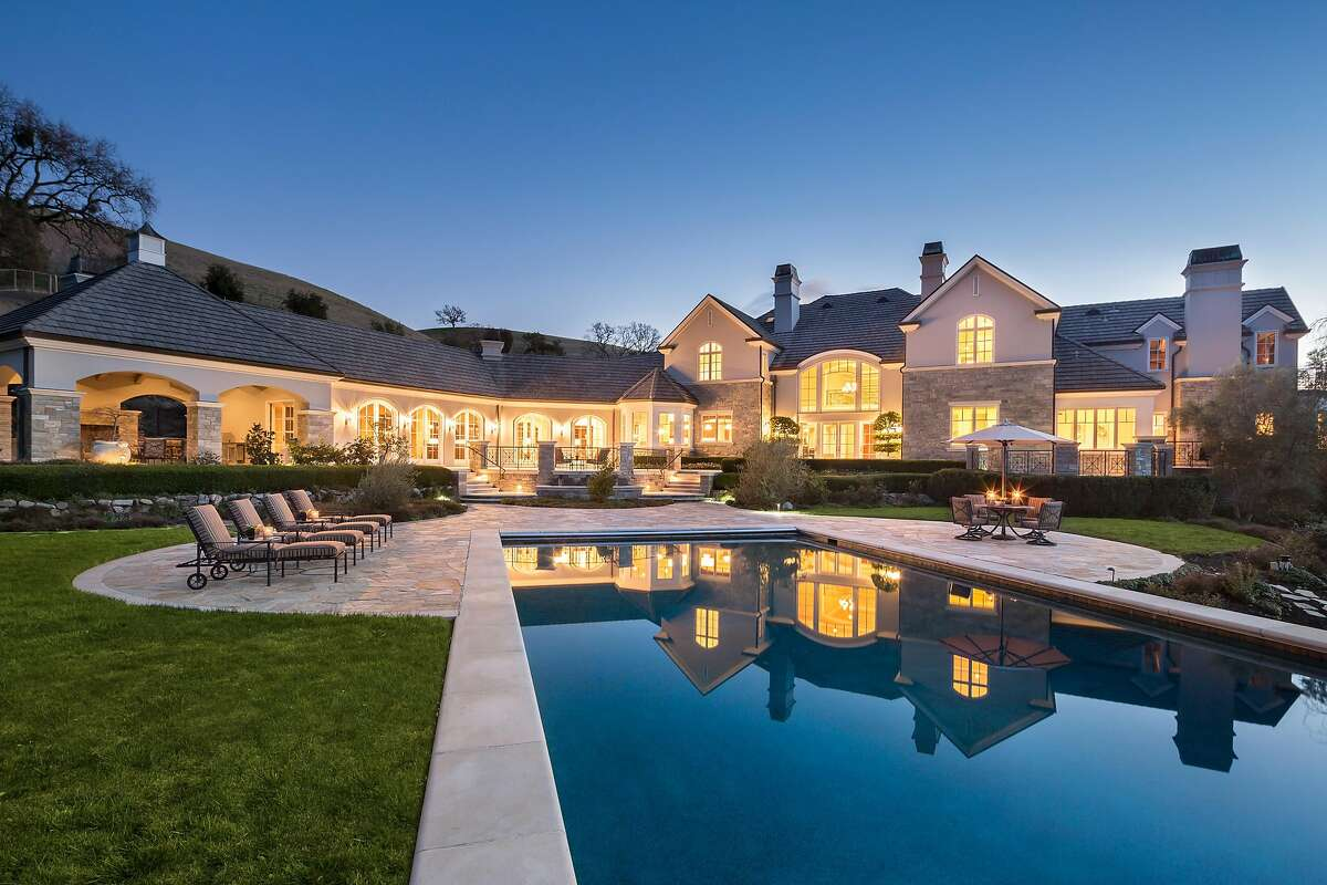 The backyard features a level lawn and an infinity edge pool.�
