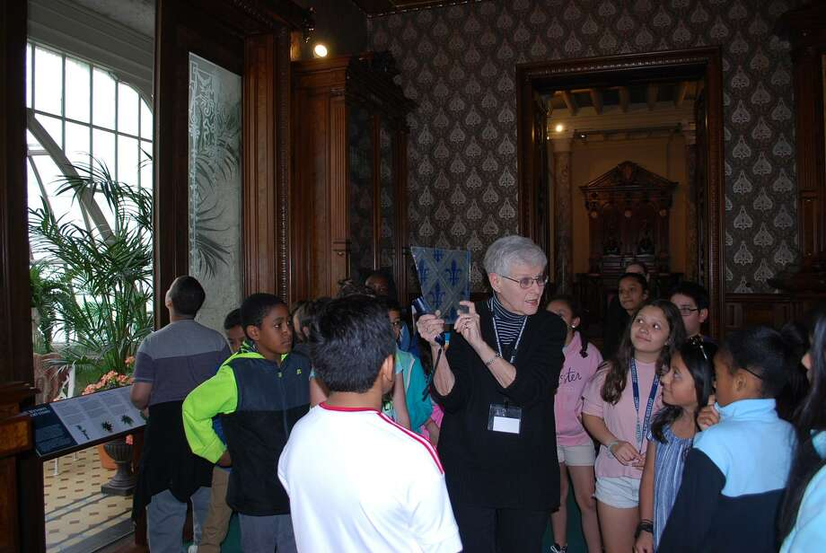 Educator and Lockwood-Mathews Mansion Museum volunteer Marilyn Bort, shows a piece of the original glass from the Conservatory to students at Jefferson Science Magnet School. Photo: Contributed Photo / Lockwood-Mathews Mansion Museum