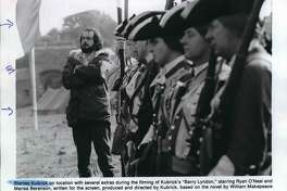 """Stanley Kubrick on location with several extras during the filming of Kubrick's """"Barry Lyndon,"""" starring Ryan O'Neal and Marisa Berenson, written for the screen, produced and directed by Kubrick, based on the novel by William Makepeace Thackeray. Patrick Magee and Hardy Kruger also star in the Warner Brothers release."""
