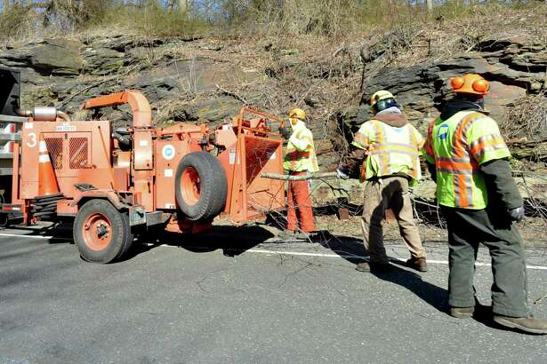 A crew with the Connecticut Department of Transportation works at chipping and cutting trees along the southbound side of the Merritt Parkway in Fairfield Conn. on Monday March 19, 2018