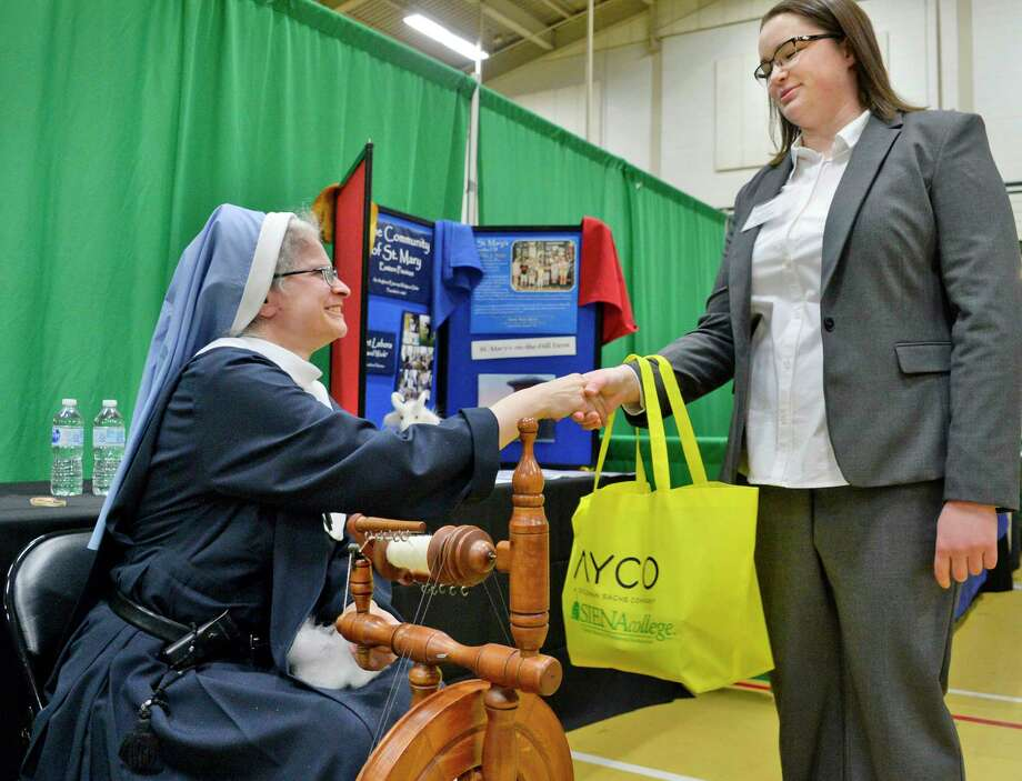 Sister Gelasia from the Community of St. Mary looks up from her spinning wheel to greet student Jordan Sumner of Selkirk during Siena College's spring career, internship and graduate school fair Tuesday March 20, 2018 in Colonie, NY.  (John Carl D'Annibale/Times Union) Photo: John Carl D'Annibale, Albany Times Union / 20043237A