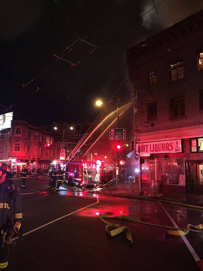 In this Saturday, March 17, 2018, photo released by the San Francisco Fire, firefighters contain a blaze on a building in the heart of San Francisco's North Beach district in San Francisco. San Francisco Fire authorities are investigating the cause of the massive building blaze that broke out during the thick of St. Patrick's Day celebrations. (San Francisco Fire via AP Photo: Associated Press