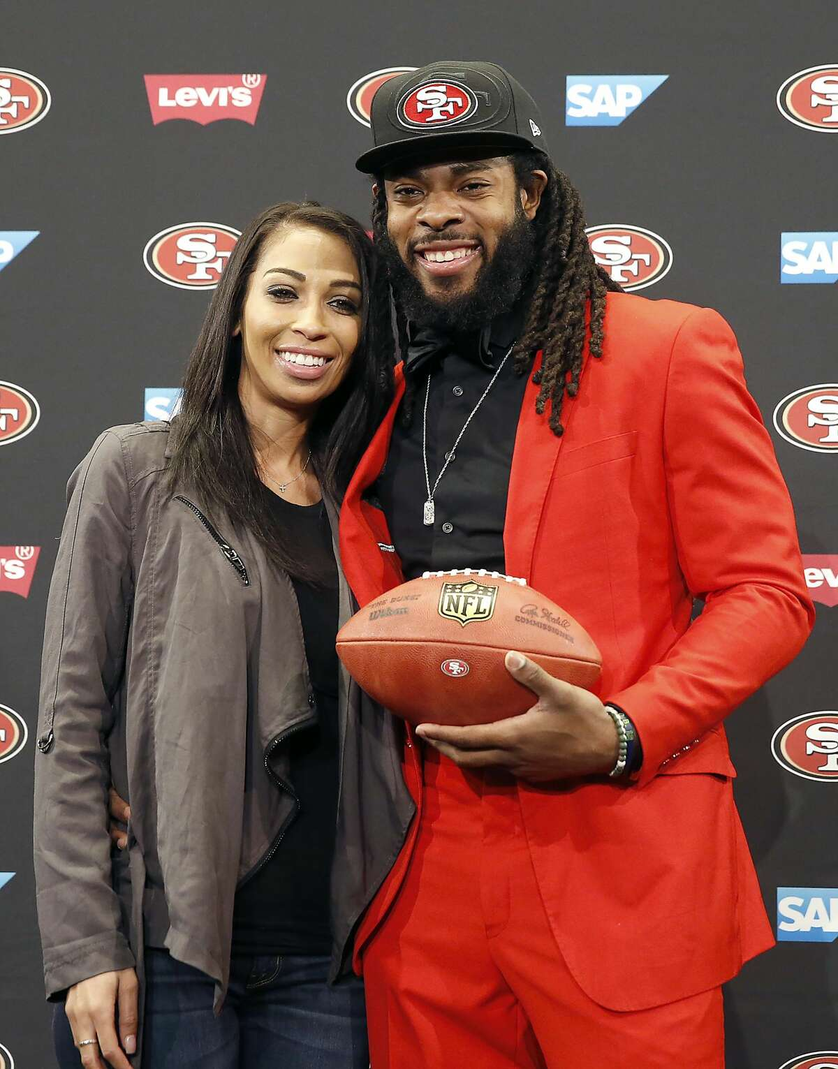 San Francisco 49ers new cornerback Richard Sherman, right, poses for a photo with his fiancee Ashley Moss after answering questions during an NFL football news conference in Santa Clara, Calif., Tuesday, March 20, 2018. Sherman agreed to a three-year deal with the 49ers.