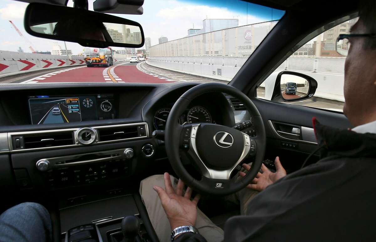 """An employee of Toyota Motor Corp., drives automated driving test vehicle during a test drive of Toyota's self-driving technologies in Tokyo, Tuesday, Oct. 6, 2015. Toyota unveiled its vision for self-driving cars in a challenge to other automakers as well as industry newcomer Google Inc., promising to start selling such vehicles in Japan by 2020. Toyota Motor Corp. demonstrated on a regular Tokyo freeway Tuesday what it called the """"mobility teammate concept,"""" meaning the driver and the artificial intelligence in a sensor-packed car work together as a team. (AP Photo/Koji Sasahara)"""