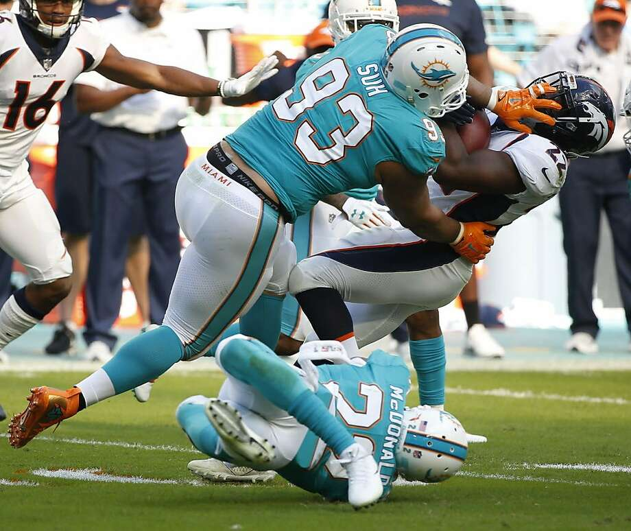 FILE - In this Dec. 3, 2017, file photo, Miami Dolphins defensive tackle Ndamukong Suh (93) and Miami Dolphins strong safety T.J. McDonald (22), tackle Denver Broncos running back C.J. Anderson (22), during the first half of an NFL football game, in Miami Gardens, Fla. The Miami Dolphins appear ready to move on without their defensive anchor. Miami is discussing releasing five-time Pro Bowl tackle Ndamukong Suh when the NFL's new year begins Wednesday, a person familiar with the situation said Monday, March 12, 2018. The person said nothing has been finalized, and confirmed the conversations to The Associated Press on condition of anonymity because the Dolphins have not commented.(AP Photo/Wilfredo Lee, File) Photo: Wilfredo Lee, Associated Press