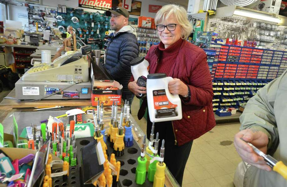 Maggie Inman grabs jugs of snow melt in preparation for the latest winter storm at Carlyn Paint and Hardware on Westport Ave. in Norwalk on Tuesday. Photo: Alex Von Kleydorff / Hearst Connecticut Media / Norwalk Hour
