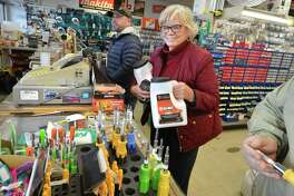 Maggie Inman grabs jugs of snow melt in preparation for the latest winter storm at Carlyn Paint and Hardware on Westport Ave. in Norwalk on Tuesday.