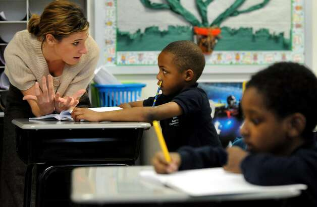 Teacher Nicole Rich, left, helps first-grader Rahcir Goggins, 6, with a writing exercise on Tuesday at Brighter Choice Charter School for Boys in Albany. Photo: CINDY SCHULTZ