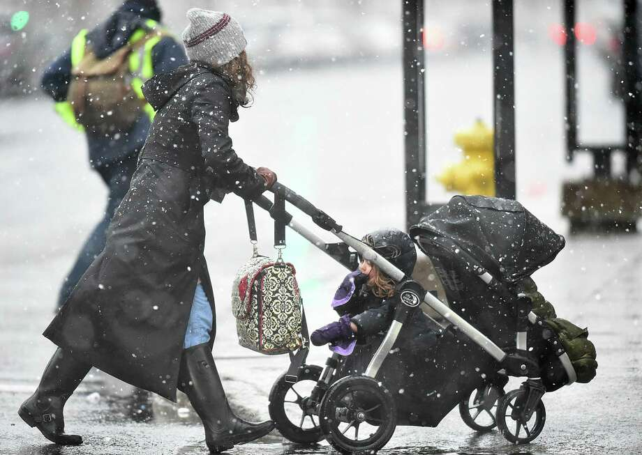 A woman pushes a child in a stroller across at the intersection of Church and Chapel Street in downtown New Haven, Wednesday, March 7, 2018, during the nor'easter predicted to bring four to eight inches of snow in the New Haven area. Photo: Catherine Avalone / Hearst Connecticut Media / New Haven Register