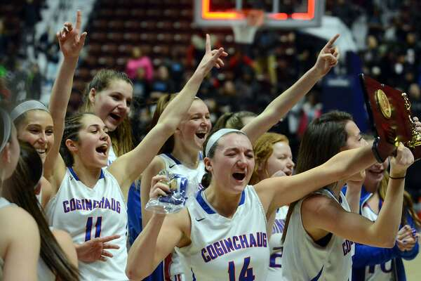 Members of the Coginchaug girls basketball team celebrate their win in the Class S championship game on Saturday in Uncasville.