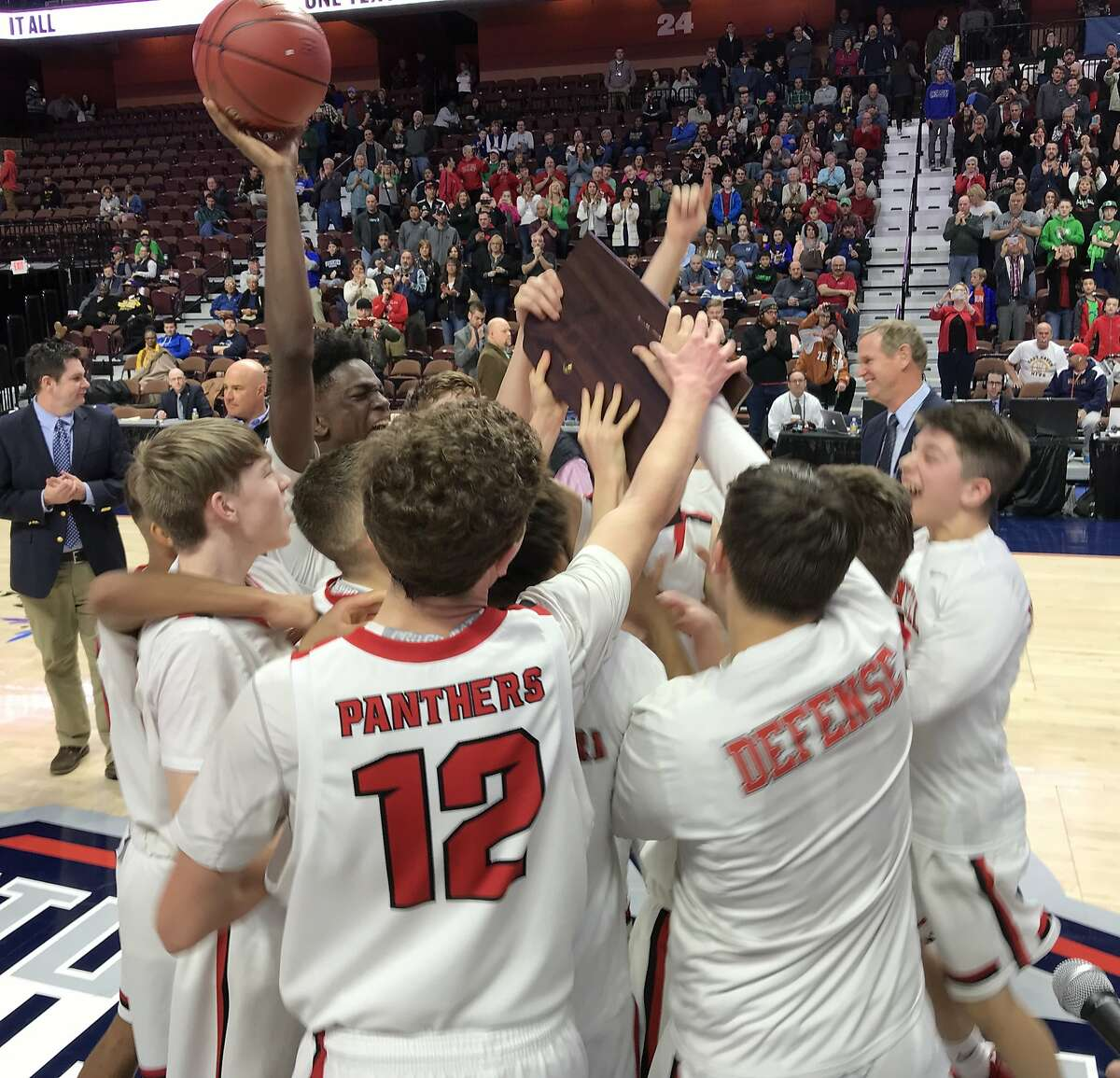 Members of the Cromwell boys basketball team celebrate with the championship plaque after their win in Saturday's Division V championship game in Uncasville.