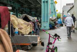 Multiple tents make up a small homeless encampment along 13th Street near Harrison Street Tuesday, March 20, 2018 in San Francisco. California's homelessness crisis requires aggressive action on lots of issues.