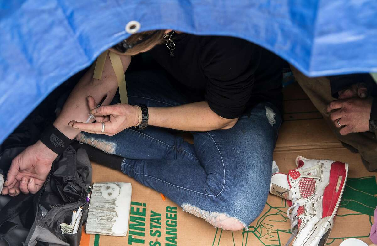Ladybird shoots up heroine inside her tent along 13th Street near Harrison Street Tuesday, March 20, 2018 in San Francisco, Calif.