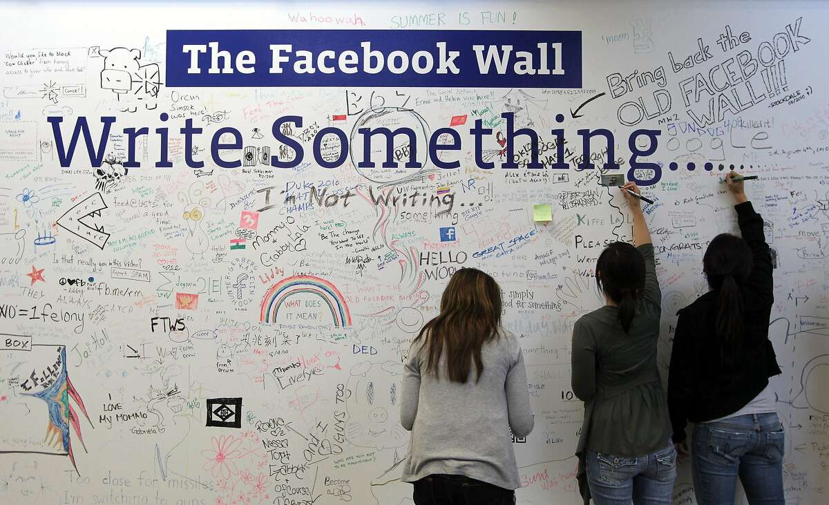 """PALO ALTO, CA - AUGUST 18: Facebook employees write on the Facebook """"wall"""" following a news conference at Facebook headquarters August 18, 2010 in Palo Alto, California. Facebook founder and CEO Mark Zuckerberg announced the launch of Facebook Places, a new application that allows Facebook users to document places they have visited. (Photo by Justin Sullivan/Getty Images)"""