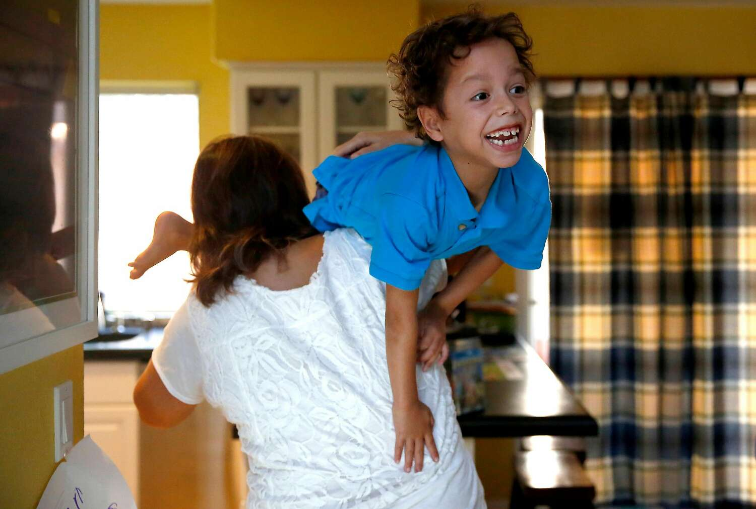 Luane carries Jordan into the kitchen to brush his teeth.