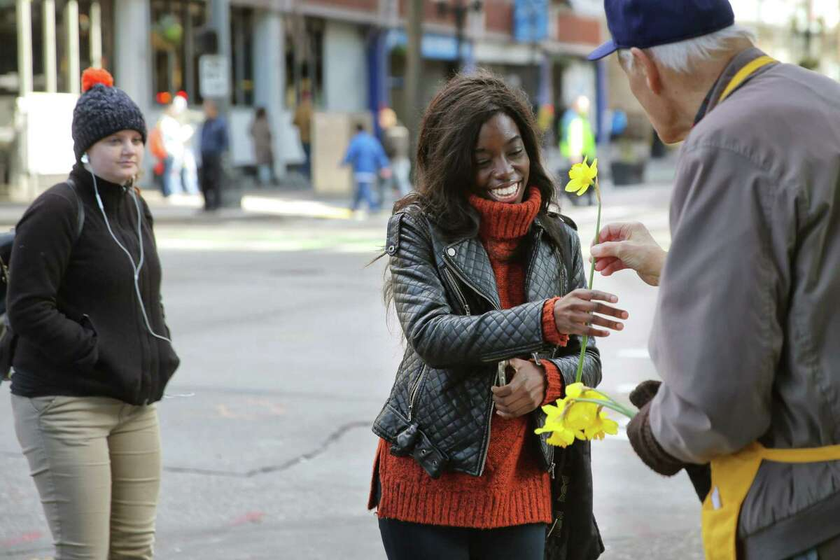 Paul Dunn hands a daffodil to Sandi Oluoch on the corner of 2nd and Pike Street, Tuesday, March 20, 2018. Dozens of volunteers handed out over 9,000 locally grown daffodils to passersby throughout downtown Seattle, Tuesday afternoon, to celebrate the first day of spring. This is the 21st annual Pike Place Market Daffodil Day.