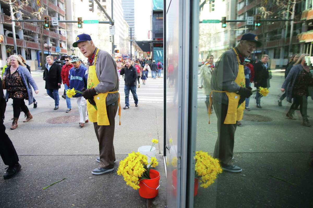 Paul Dunn hands out daffodils to passersby on corner of 2nd and Pike Street, Tuesday, March 20, 2018. Dozens of volunteers handed out over 9,000 locally grown daffodils to people throughout downtown Seattle, Tuesday afternoon, to celebrate the first day of spring. This is the 21st annual Pike Place Market Daffodil Day.