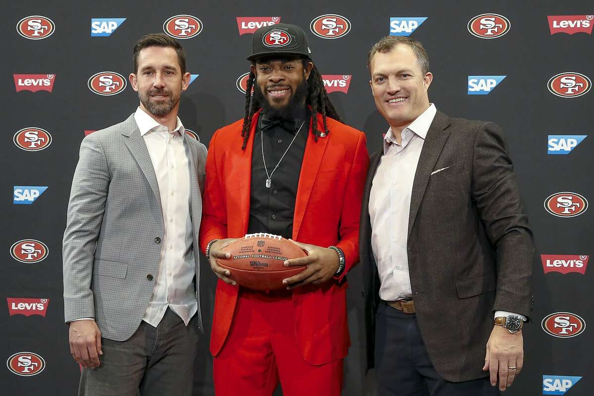San Francisco 49ers head coach Kyle Shanahan, left, cornerback Richard Sherman, center, and general manager John Lynch, right, pose for a photo before an NFL football news conference in Santa Clara, Calif., Tuesday, March 20, 2018.