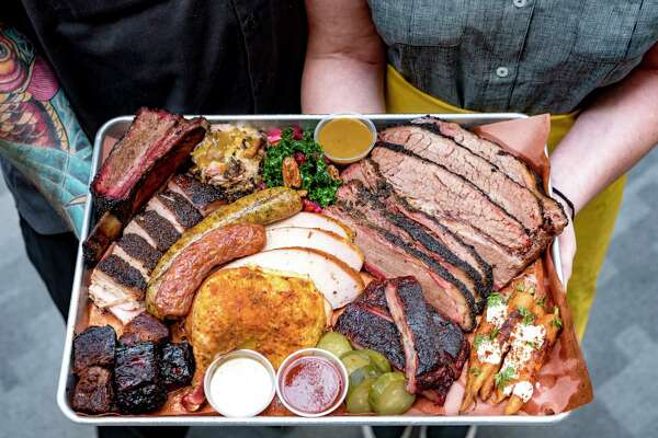 A sampler from Feges BBQ in Houston. Clockwise from top left: Beef short ribs; pulled pork; kale salad; mustard sauce; sliced brisket; Moroccan spiced carrots; pork ribs; pickles; sweet barbecue sauce; Alabama white sauce; beef belly burnt ends; pork belly. Center: Smoked half chicken; boudin; sausage.