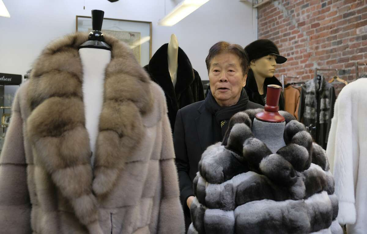 In this photo taken Friday, March 16, 2018, Benjamin Lin poses by fur coats at the B.B. Hawk showroom in San Francisco. San Francisco could become the largest U.S. city to ban the sale of fur items, a move that would hearten animal lovers but frustrate niche business owners who say they're fed up with a city that dictates what retailers can or can't sell. If the ban is approved by the Board of Supervisors on Tuesday, March 20, 2018, San Francisco would join two other California cities, West Hollywood and Berkeley, in saying no to a symbol of glamour that animal advocates say is built on cruelty and doesn't reflect the city's values. (AP Photo/Eric Risberg)