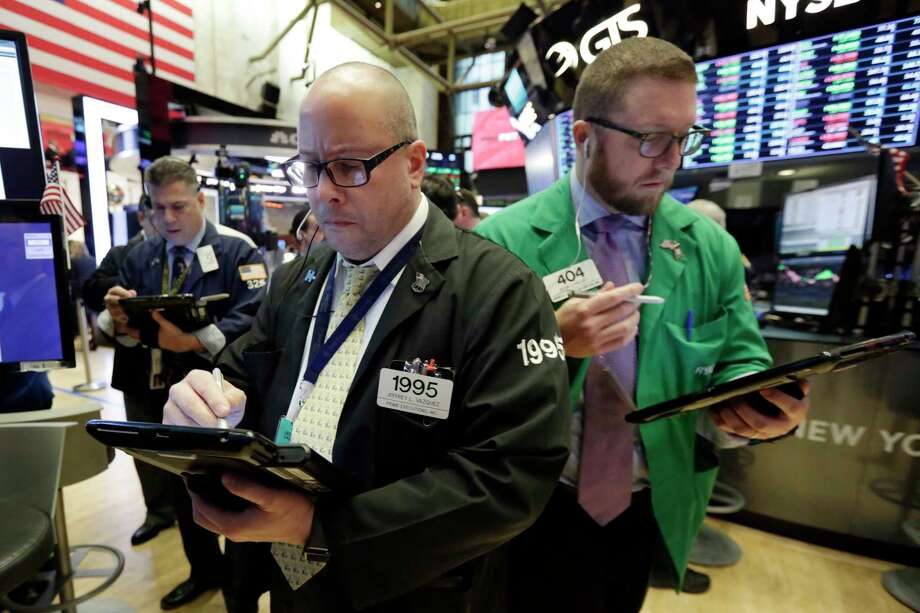 Traders Jeffrey Vazquez, center, and Ryan Falvey, right, work on the floor of the New York Stock Exchange, Tuesday, March 20, 2018. Banks and energy stocks are leading early gains for U.S. indexes. (AP Photo/Richard Drew) Photo: Richard Drew / AP