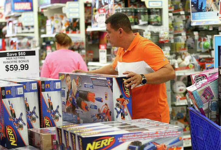 """A customer shops for his nephews during Black Friday 2017 inside Toys """"R"""" Us in Friendswood, Texas."""