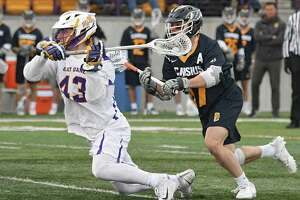 University at Albany's Josh Egan is defended by Canisius' Michael Sanzone as he takes a shot while falling to the ground during a lacrosse game at Casey Stadium on Tuesday, March 20, 2018 in Albany, N.Y. (Lori Van Buren/Times Union)