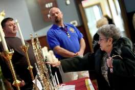 """East Haven resident Tootsie Franco, 87,  touches a glove worn by Saint Padre Pio at the time of his death, on display at Our Lady of Pompeii Church in East Haven Tuesday. Franco, clutching a scapular of St. Padre Pio, said, """"Padre Pio is someone I pray to."""" At left is cantor Joe Silva, and at right is Mike Vittoria, Our Lady of Pompeii K of C Council 11245."""