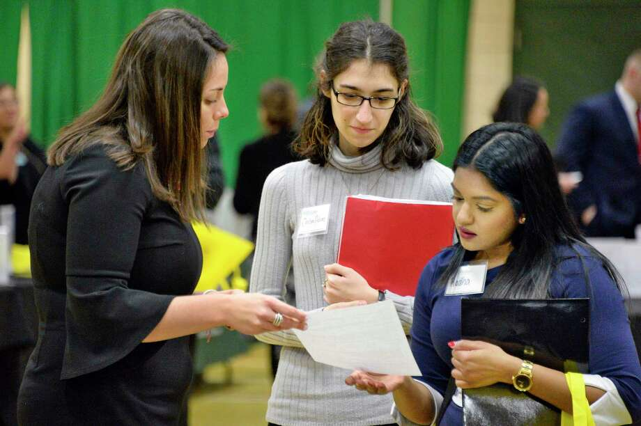 AYCO recruiter Jillian Sosamino, left, speaks with students Chelsea Adams and Radha Persaud, right, during Siena College's spring career, internship and graduate school fair Tuesday March 20, 2018 in Colonie, NY.  (John Carl D'Annibale/Times Union) Photo: John Carl D'Annibale / 20043237A