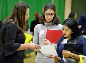 AYCO recruiter Jillian Sosamino, left, speaks with students Chelsea Adams and Radha Persaud, right, during Siena College's spring career, internship and graduate school fair Tuesday March 20, 2018 in Colonie, NY.  (John Carl D'Annibale/Times Union)