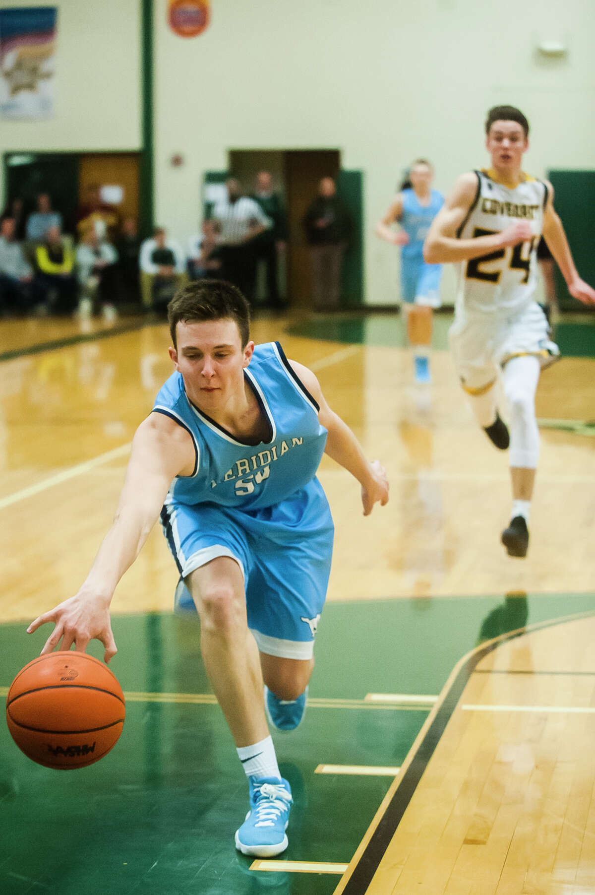 Meridian junior Gabe Brady lunges forward to keep the ball in bounds during the Mustangs' 53-30 loss to Grand Rapids Covenant Christian in the Class C state semifinals on Tuesday, March 20, 2018 at Central Montcalm High School in Stanton. (Katy Kildee/kkildee@mdn.net)