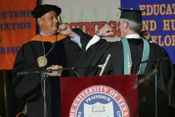 """University of Texas at San Antonio President Taylor Eighmy, left, greets University of Texas System Chancellor William H. McRaven with """"The Wing"""" greeting during Eighmy's inauguration ceremony at the Convocation Center, Tuesday, March 20, 2018."""