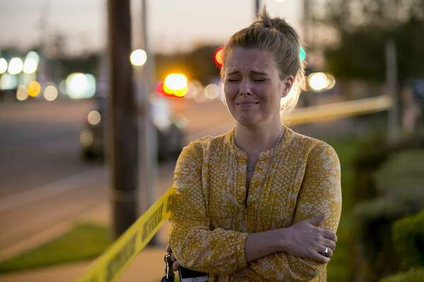 Caity Colvard gets emotional as she watches a massive response of law enforcement officers at a bomb explosion site at a Goodwill store in Austin, Texas, on Tuesday March 20, 2018.  Emergency teams were responding  to another reported explosion in Texas' capital, this one at a Goodwill store in the southern part of the city. (Jan Janner/Austin American-Statesman via AP)