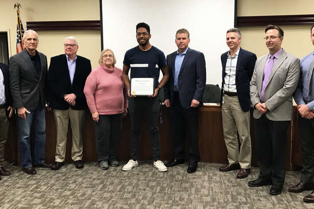 EHS senior student Marcus Kwasa, center, poses with city aldermen and Edwardsville Mayor Hal Patton after receiving a commendation award at Tuesday's City Council meeting.