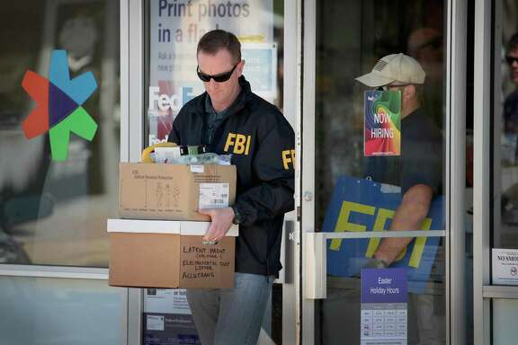 SUNSET VALLEY, TX - MARCH 20:  FBI agents collect evidence at a FedEx Office facility following an explosion at a nearby sorting center on March 20, 2018 in Sunset Valley, Texas. A package, reported to have been shipped from this store, exploded while being transported on a conveyor shortly after midnight this morning at the sorting facility in Schertz, Texas causing minor injuries to one person. The explosion is believed to be related to several recent package bombs that have been detonated in Austin, Texas.  (Photo by Scott Olson/Getty Images)