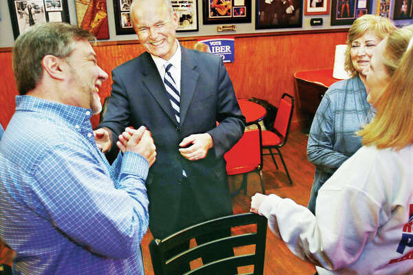Democratic candidate for Illinois Governor, Bob Daiber, center, shares a laugh with well-wishers Tuesday night at Donzo's Bar on East Ferguson Avenue in downtown Wood River after the polls closed. A group of family and friends gathered for a watch party at the establishment to monitor the primary race. Chicago billionaire J.B. Pritzker was deemed the winner of the Democratic nomination by numerous news outlets late Tuesday.