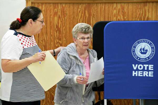 Election inspector Helen Barber, left, helps voter Mary Powell to cast her ballot Tuesday March 20, 2018 in Ravena, NY.  (John Carl D'Annibale/Times Union)