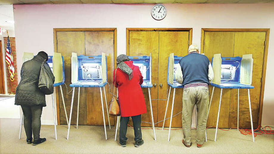 Several voters came in to vote right after lunchtime Tuesday at the Messish Lutheran Church in Alton where voters in the Alton 6th, 16th and 24th precincts cast their ballots. Here three voters take their time while voting together in the 16th precinct. Photo: John Badman | The Telegraph