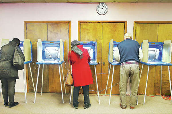 Several voters came in to vote right after lunchtime Tuesday at the Messish Lutheran Church in Alton where voters in the Alton 6th, 16th and 24th precincts cast their ballots. Here three voters take their time while voting together in the 16th precinct.