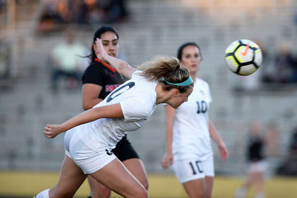 Nederland's Meg Sheppard attempts to head the ball against Memorial at Bulldog Stadium on Tuesday evening.  Photo taken Tuesday 3/20/18 Ryan Pelham/The Enterprise