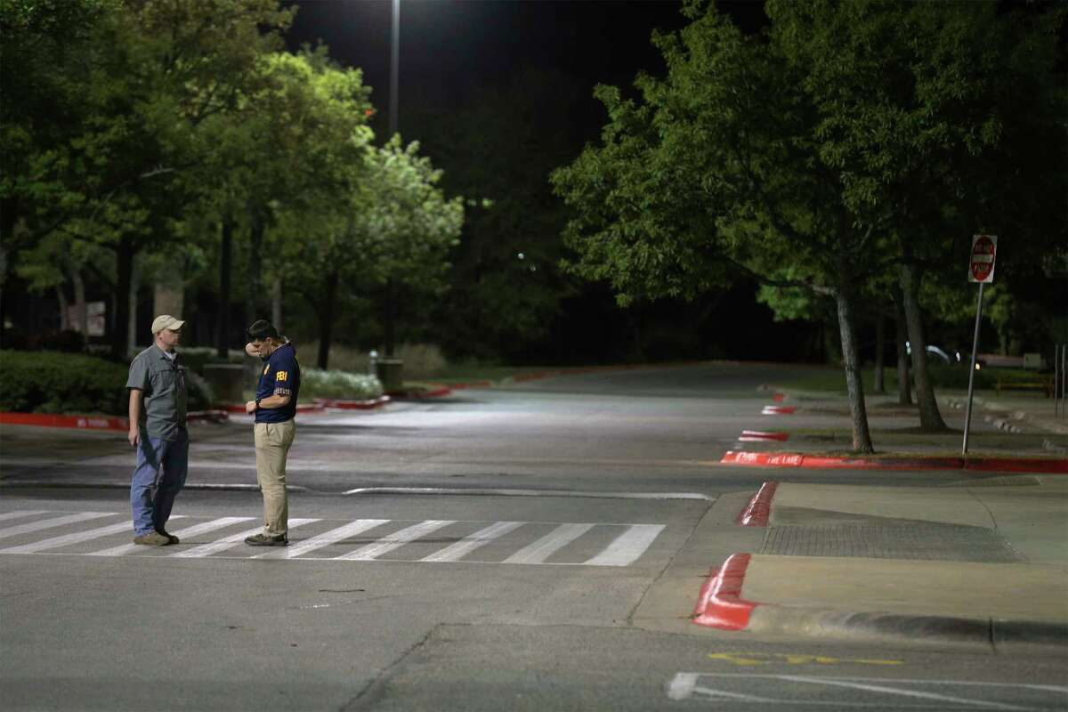 An FBI official along with an individual stand in the street near a Randall's along Slaughter and Brodie Lanes in South Austin near where an incendiary device caused law enforcement to be alarmed that another bomb had been discovered on Tuesday, Mar. 20, 2018. Officials stated that the device was not linked to the series of bombings that have occurred in Austin that has taken lives and forced the community to be on high alert.