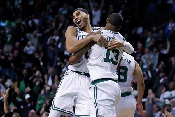 Boston Celtics forward Marcus Morris (13) leaps into the arms of teammate Jayson Tatum as they celebrate Morris' game-winning 3-point shot in the team's NBA basketball game against the Oklahoma City Thunder in Boston, Tuesday, March 20, 2018. The Celtics won 100-99. (AP Photo/Charles Krupa)