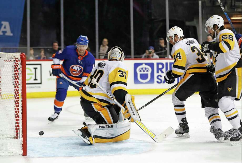 New York Islanders right wing Josh Bailey (12), Pittsburgh Penguins right wing Tom Kuhnhackl (34) of Germany and Penguins defenseman Kris Letang (58) watch as the puck rolls behind Pittsburgh Penguins goaltender Matt Murray (30) during the second period of an NHL hockey game in New York, Tuesday, March 20, 2018. (AP Photo/Kathy Willens) Photo: Kathy Willens / Copyright 2018 The Associated Press. All rights reserved.