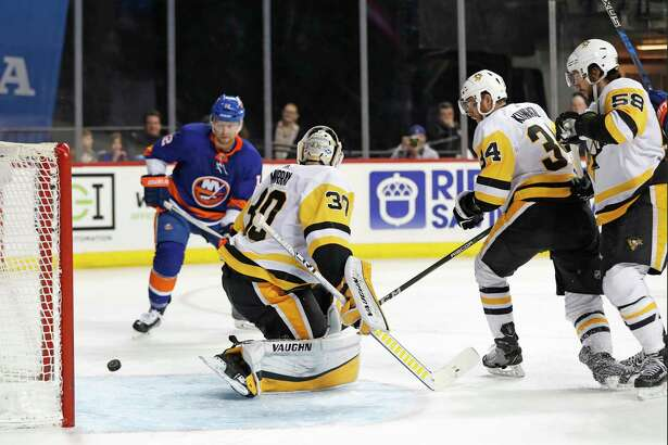 New York Islanders right wing Josh Bailey (12), Pittsburgh Penguins right wing Tom Kuhnhackl (34) of Germany and Penguins defenseman Kris Letang (58) watch as the puck rolls behind Pittsburgh Penguins goaltender Matt Murray (30) during the second period of an NHL hockey game in New York, Tuesday, March 20, 2018. (AP Photo/Kathy Willens)