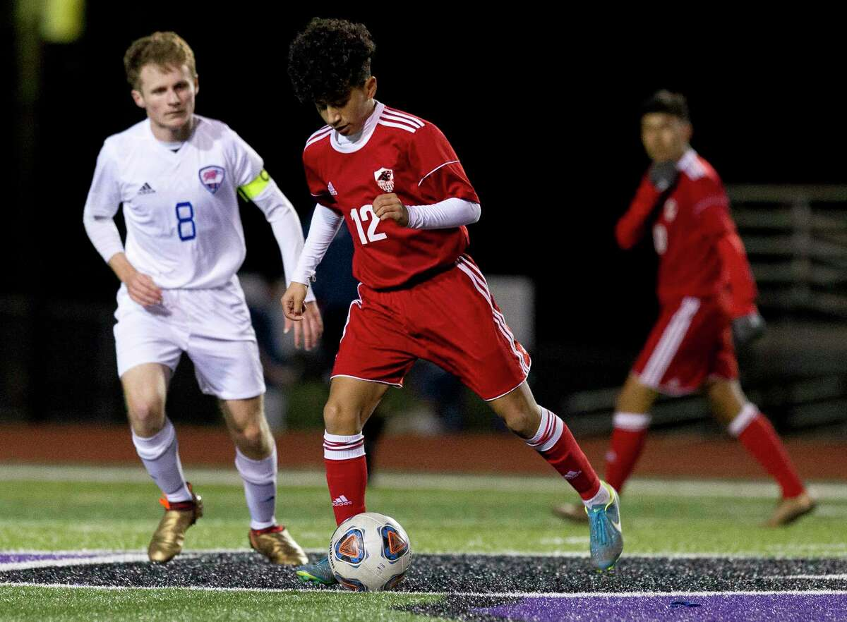 Caney Creek's Ulysses Cruz (12) works the ball against Oak Ridge's Ewan Laing (8) in the first period of a match during the Willis Wildkat Showcase at Lynn Lucas Middle School, Thursday, Jan. 4, 2018, in Willis.