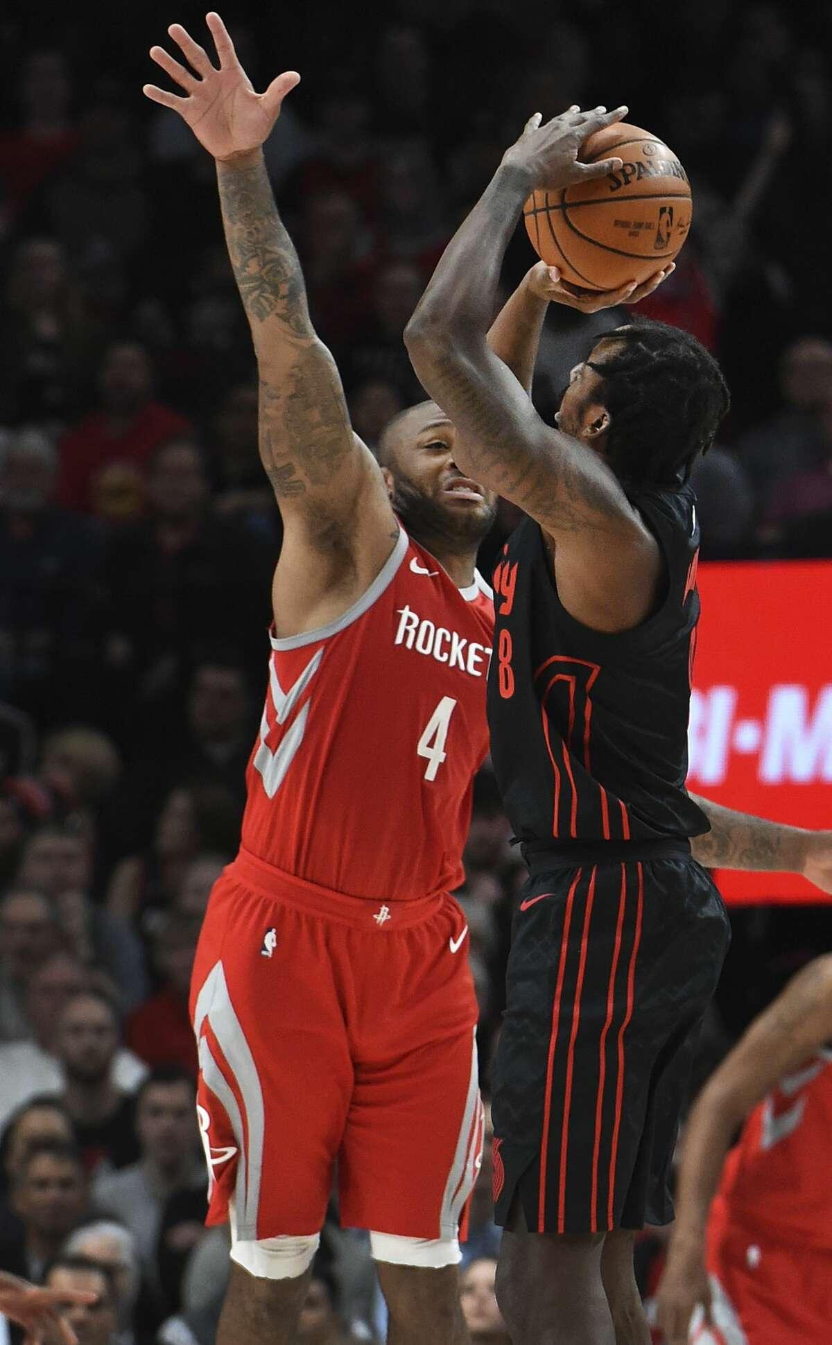 Portland Trail Blazers forward Al-Farouq Aminu hits a 3-point shot over Houston Rockets forward PJ Tucker during the first half of an NBA basketball game in Portland, Ore., Tuesday, March 20, 2018. (AP Photo/Steve Dykes)