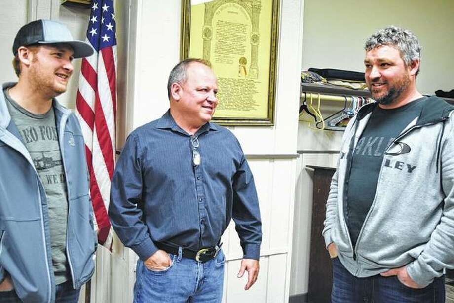 Mike Carmody (center) talks with Luke Cantrell (left) and Jason Evans Tuesday at the Knights of Columbus Hall as he awaits election results.