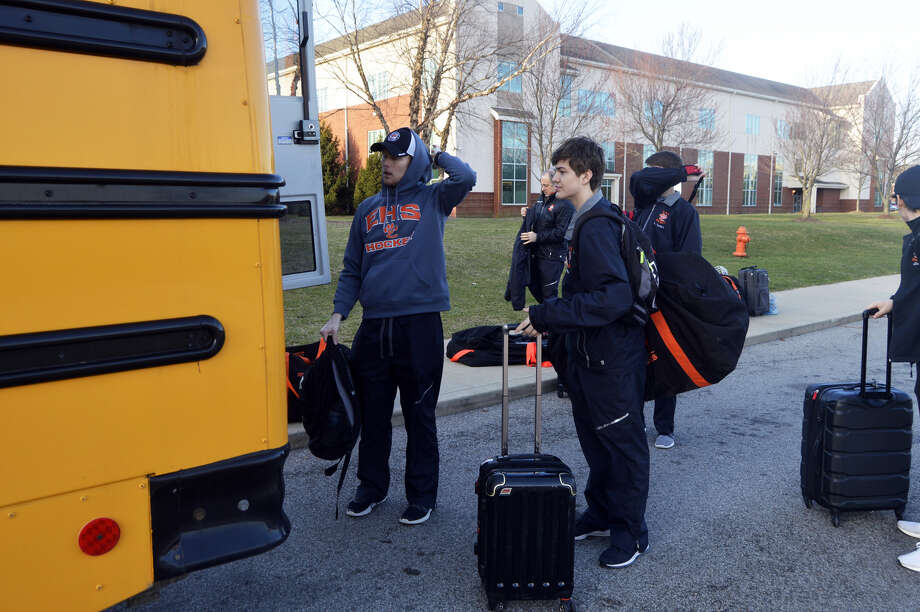 Edwardsville coach Jason Walker, left, and senior Stanley Lucas, right, start packing the bus for the trip to the airport Wednesday morning behind Edwardsville High School.