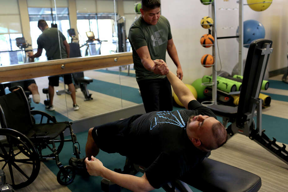 Steven Herrera gives a hand to his roommate, Isaac Rodriguez, as they exercise in their apartment complex gym on Tuesday, March 20, 2018. After Isaac's amputation, his balance was off so Steven helped him with the weights. Photo: SAN ANTONIO EXPRESS-NEWS / SAN ANTONIO EXPRESS-NEWS